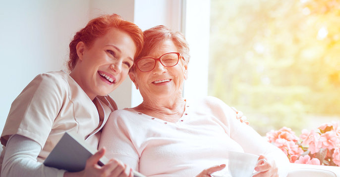 happy elder woman and caregiver