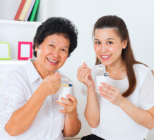 elder woman and a young woman eating yoghurt