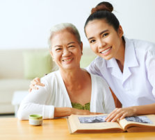 elder woman and her caregiver smiling