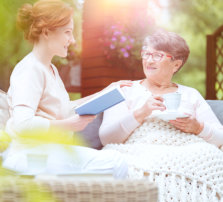 caregiver reading a book to an elder woman