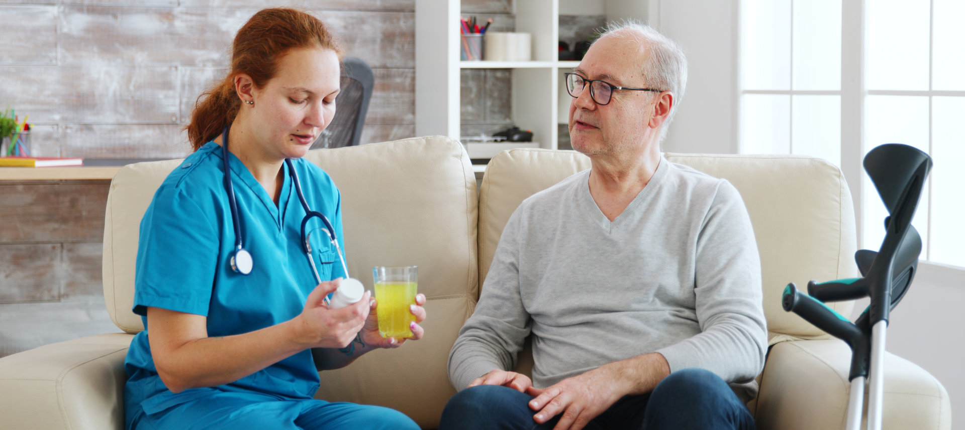 home nurse is giving daily pills to old man